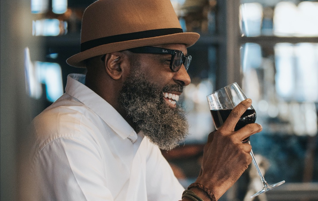 Image of a smiling middle-aged man with a beard wearing a brown fedora hat drinking red wine in a restaurant.