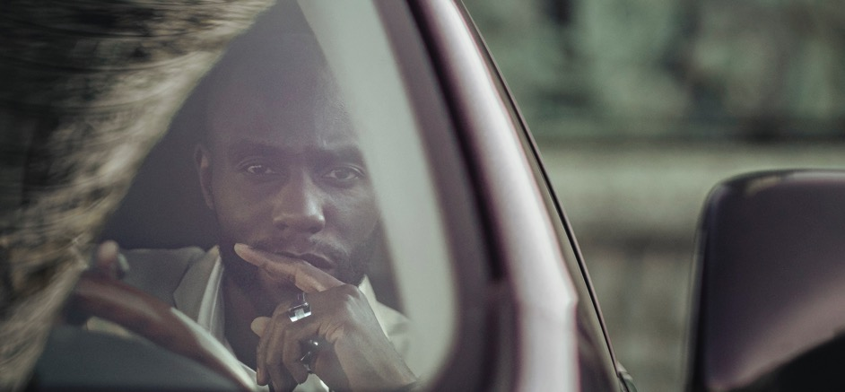 Image of a man sitting behind the wheels of his car looking at the camera.