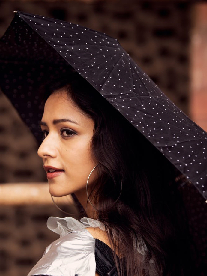 Side profile of a woman holding a speckled umbrella.